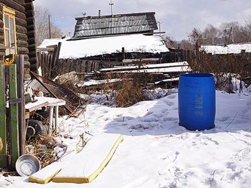 Дождевая бочка во дворе садового домика семьи Кузьминых, где неделю пролежал труп Говорухиной