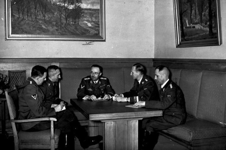 Совещание по результатам расследования покушения Георга Эльзера на Гитлера в помещении «Бюргербройкеллер» в Мюнхене 8 ноября 1939 года. Слева направо: оберштурмбаннфюрер СС Франц Йозеф Хубер[de], оберфюрер СС Артур Небе, рейхсфюрер СС Генрих Гиммлер, груп