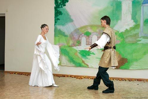 Средневековый танец молодожёнов на фоне декорации, нарисованной Анастасией